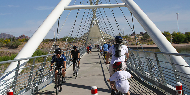 multiple people riding their bikes across the Tempe Bridge